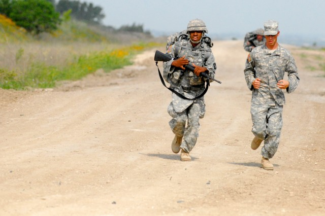 Cpl. Jayme Hestermann runs alongside his battle buddy to help motivate Spc. Antoine Mitchell, from the 4th Sustainment Brigade, 13th Sustainment Command (Expeditionary), during the second day of the Wrangler Brigade Soldier and NCO of the year competition at Fort Hood, Texas May 11. (U.S. Army photo by Sgt. Angiene L. Myers)
