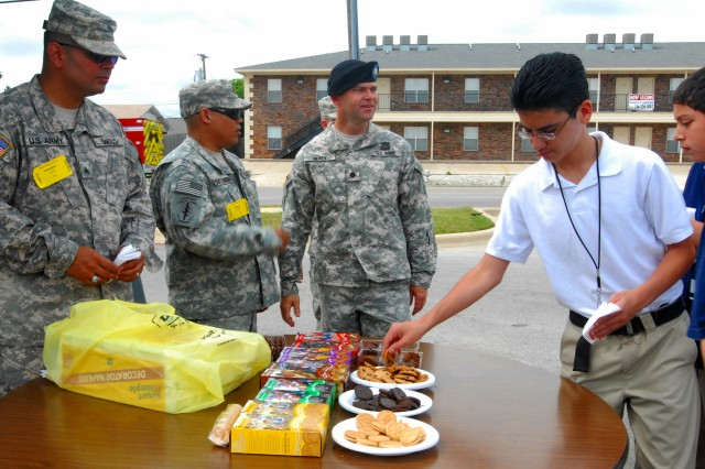 Lt. Col. John Hickey, the commander of the 4th Brigade Troops Battalion, watched his Soldiers in action as Soldiers, from the 4th Sustainment Brigade, 13th Sustainment Command (Expeditionary), fed students at Nolan Middle School in Killeen, Texas snacks of Girl Scout cookies donated by the unit's Family Readiness Group as a part of the unit's Adopt-A-School program May 25. (U.S. Army photo by Pfc. Amy M. Lane)