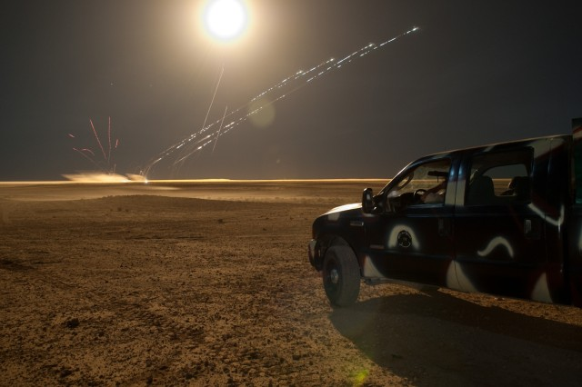 AL ASAD AIR BASE, Iraq - A flare lights up the night for helicopters attacking ground targets with rockets on a firing range outside Al Asad Air Base, Iraq, as soldiers with the 27th Brigade, 7th Iraqi Army Division, watch from their gun truck, May 21. The soldiers took part in a three-day course to teach them fire support skills. (U.S. Army photo by Sgt. Michael J. MacLeod, 1/82 AAB, USD-C)