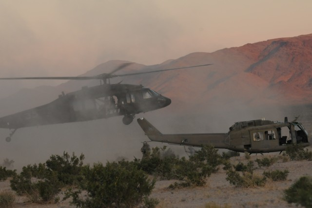 """Soldiers from 4th Squadron, 3rd Armored Cavalry Regiment, position their UH-60 Blackhawk helicopter to slingload the shell of a UH-1 Iroquois """"Huey"""" helicopter at the U.S. Army National Training Center at Fort Irwin, Calif., May 28. (Army Photo by Pfc. Jennifer Spradlin, 16th Mobile Public Affairs Detachment)"""