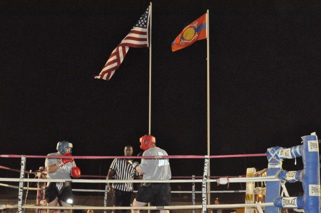 """Two members of Task Force Phoenix, 3rd Brigade Special Troops Battalion, 3rd Brigade Combat Team, 4th Infantry Division, compete in the """"Final Chapter"""" of Bucca Boxing at Camp Bucca, Iraq, May 15, 2010.  The U.S. colors fly with the Camp Bucca flag in the background on the poles dedicated to retired Marine Corps Master Sgt. Felix E. Colman.  Felix worked for the past three years as a civilian contractor at the camp information technologies department and was the main organizer of Bucca Boxing."""