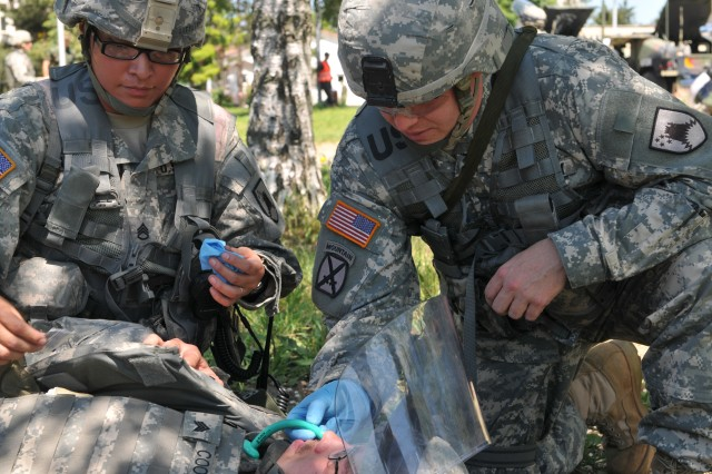 Staff Sgt. Ciciley R. Littlewolf, Wahpeton, N.D., watches as Spc. John D. Kotaska, Grand Forks, N.D., inserts a nasopharyngeal airway (NPA) during an exercise at Camp Monteith, Kosovo. Sgt Chris J. Coombs, Moorhead, Minn., was deemed a simulated casualty, with a chest wound, that the medics and combat lifesavers inserted an NPA and was given an IV to simulate real-life scenarios.