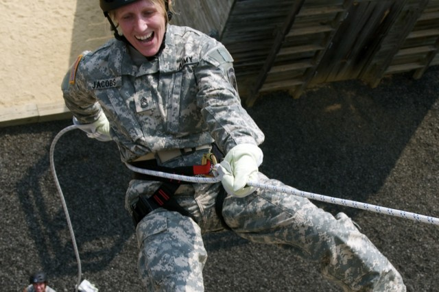 Sgt. 1st Class Kim Jacobs, intelligence analyst for the U.S. Army Civil Affairs and Psychological Operations Command (Airborne), rappels off a wall during a confidence-building obstacle course, May 16.