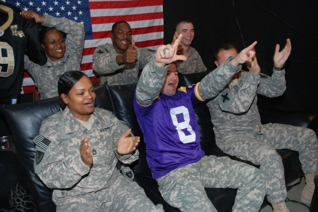 Soldiers stationed at Joint Base Balad, Iraq react as they appear live on the giant screen at Louisiana State University's Tiger Stadium during the Memorial Day weekend Bayou Country Superfest in Baton Rouge, La., May 31. The Soldiers are (front row, left to right) Sgt. 1st Class Barbara Bossier, first sergeant, Headquarters and Headquarters Detachment, 402nd Army Field Support Brigade, who hails from Lafayette, La., and is with the Army Reserve's 377th Theater Support Command in New Orleans; Staff Sgt. Dustin Borque (sporting an LSU jersey), from Breaux Bridge, La., a Security Forces Operations noncommissioned officer, HHC, 256th IBCT, Louisiana National Guard; Master Sgt. Paul Bordelon, Marksville, La., Security Forces Operations noncommissioned officer-in-charge, HHC, 256th IBCT, Louisiana National Guard; (second row, left to right) Spc. Ishiah Mouton, Lafayette, La., Security Forces convoy tracker, HHC, 256th IBCT, Louisiana National Guard; Sgt. 1st Class Rhonda Lawson, Public Affairs officer, HHC, 3rd Special Troops Battalion, 3rd Sustainment Brigade, Fort Stewart, Ga., whose hometown is New Orleans; and Spc. Austin Lumpkin, HHC, 36th Engineer Brigade, Fort Hood, Texas, who is from Belle Chasse, La.