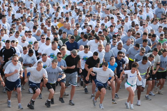 "Participants surge across the starting line at Holt Stadium as a ""shadow run"" version the 31st Annual Huntsville (Ala.) Cotton Row Run kicks-off on Joint Base Balad, May 31. More than 1,000 runners took part."