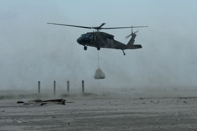 UH-60 Black Hawk helicopters belonging to the 1/244th Assault Helicopter Battalion, State Aviation Command, Louisiana Army National Guard, in Hammond, La., sling load several 1,000-pound sandbags to Trinity Island to fill in a low-lying area critical to oil spill mitigation efforts along Louisiana's shoreline, May 27. Trinity Island is one of many barrier islands along the coast of Louisiana threatened by the oil spill.