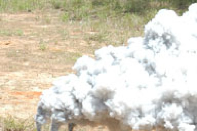 """Firemarkers watch from the woodline as a """"smoke pot"""" fills a battlefield with smoke at the Joint Readiness Training Center May 18."""