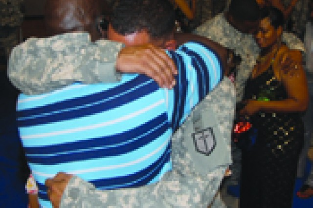 Spc. Robert Cushionberry Jr. receives a hug from his father, Robert Cushionberry Sr.