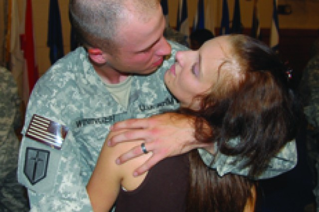 Spc. Charles Wininger is about to kiss his wife, Donna, at the homecoming event May 24.
