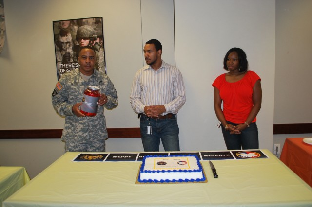 Sgt. Maj. Anthony Taylor, U.S. Army Reserve Command (USARC) G-1 sergeant major, accepts the Enlisted Dining Out donation from USARC interns, Scott Sutton and Relandra Rhone. The two gathered more than $200 to help underwrite the cost for junior Soldiers to attend the dinner night.