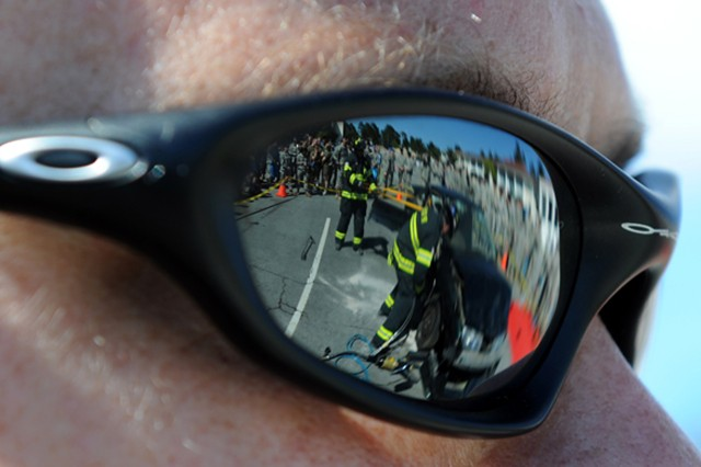 PRESIDIO OF MONTEREY, Calif. - POM firefighter Sean Haggerty looks on as his peers tear apart a vehicle to demonstrate their method of extracting casualties during Safety Day, as reflected in his glasses.