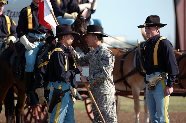 FORT HOOD, Texas-Maj. Gen. Daniel Allyn (center), 1st Cavalry Division's commanding general, hands Capt. David Jackson, of Jacksonville, Texas, the unit guidon, during the Horse Cavalry Detachment's Change-of-Command ceremony May 27, as Jackson takes over from Capt. Jay Bunte (right).