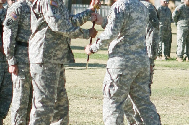 Command Sgt. Maj. Todd Holiday, U.S. Army Intelligence Center of Excellence and Fort Huachuca, and the Military Intelligence Corps command sergeant major, accepts the noncommissioned officers' sword from Maj. Gen. John Custer, commanding general, USAICoE and Fort Huachuca during the change of responsibility ceremony, held today, on Brown Parade Field.
