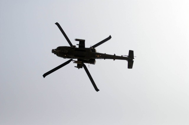 "An AH-64D Apache with Company C, 1st Attack Reconnaissance Battalion, 1st Aviation Regiment, Task Force 12 glides effortlessly over Memorial Hall during the Memorial Day Ceremony held at Contingency Operating Base Adder, Iraq, May 31. The Apache peeled off from the three aircraft formation after passing over to represent the ""missing man"" in a formation."