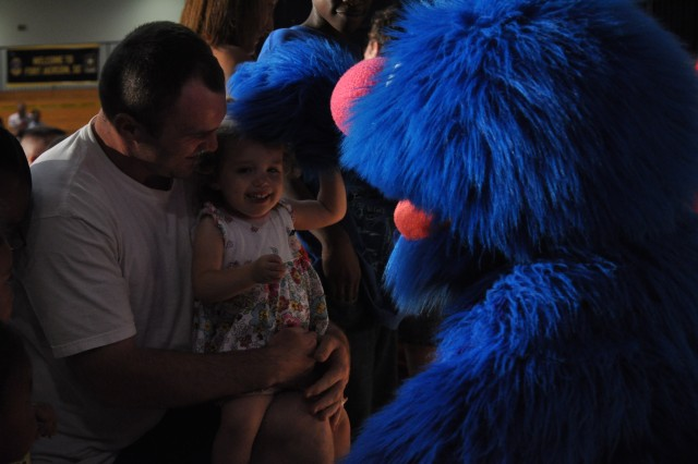 Leanna Singleton, 2, is all smiles as she greets Grover during the Sesame Street show Friday night.