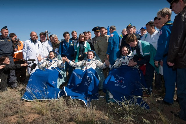 Three Expedition 23 crew members have just been seated in chairs near their Soyuz TMA-17 spacecraft just minutes after they landed near the town of Zhezkazgan, Kazakhstan, on June 2, 2010. In the chairs, from the left, are Japan Aerospace Exploration Agency astronaut Soichi Noguchi, Russian cosmonaut Oleg Kotov and NASA astronaut T.J. Creamer. The three are returning from six months onboard the International Space Station where they served as members of the Expedition 22 and 23 crews. The crowd includes NASA astronaut managers and other astronauts, along with other officials.