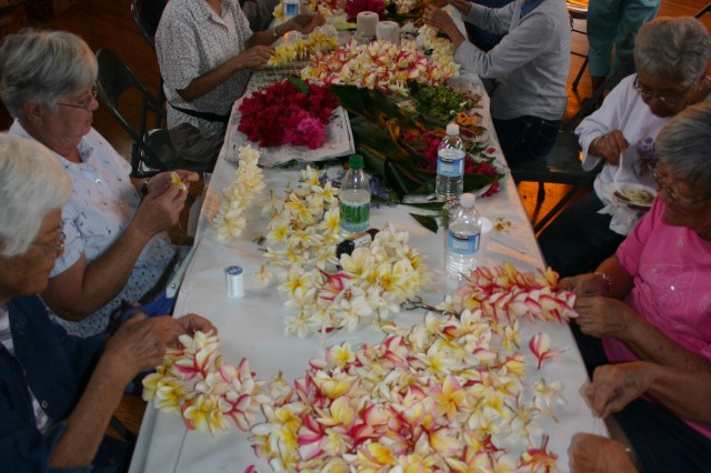 WAHIAWA, Hawaii - Surrounded by fresh flowers, members from the Wahiawa Rainbow Seniors club gather at the Wahiawa Hongwanji Mission to string 1,765 lei for gravesites.