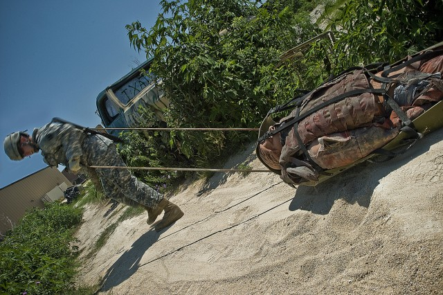 FORT HOOD, Texas-With a simulated casualty in tow, Wharton, Texas native Sgt. Timothy Long muscles his 250 pound dummy towards a designated extraction point during the 1st Cavalry Division Non Commissioned Officer and Soldier of the Year Competition, June 1. Long is a shop foreman with the 220th Field Artillery Regiment, 41st Fires Brigade.