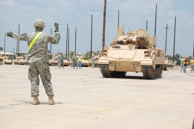 FORT HOOD, Texas - Sgt. Erik Saathoff, an infantryman from Houston, Texas, assigned to the 2nd Battalion, 12th Cavalry Regiment, 4th Brigade Combat Team, 1st Cavalry Division, guides a track vehicle onto a rail car at the rail operations center, June 2.