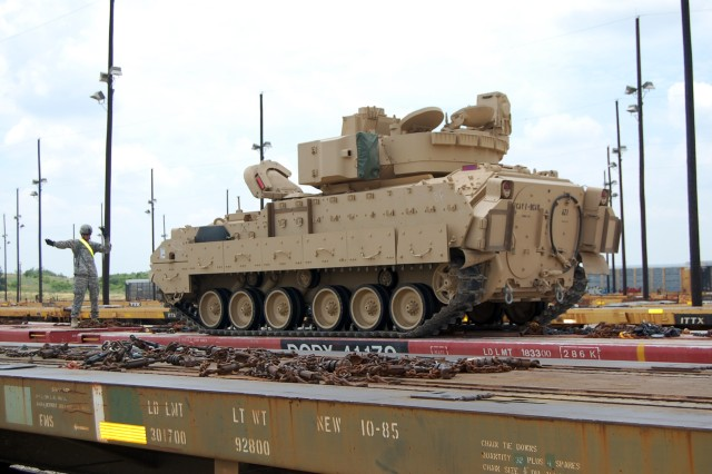 FORT HOOD, Texas - Sgt. Jeremy Norton, a cavalry scout from Clarksville, Tenn., assigned to the 1st Squadron, 9th Cavalry Regiment, 4th Brigade Combat Team, 1st Cavalry Division, guides a track vehicle onto a rail car at the rail operations center, June 2.