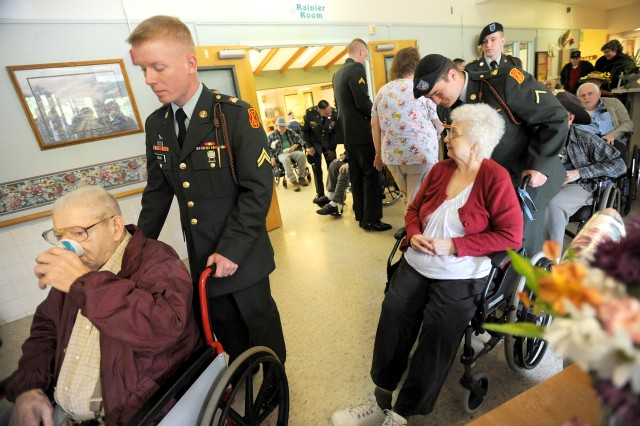 Cpl. Nathaniel Bratt, left, and Pvt. 2 Benjamin Taylor wheel residents of the Washington State Soldiers Home to a Memorial Day program at the facility put on by the 1-94 FA unit, Monday.
