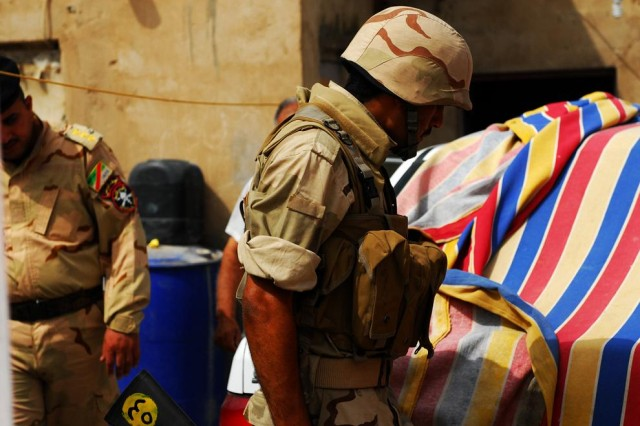 Soldiers with the 14th Iraqi Army Division, 52nd Brigade, look for weapons and bomb-making materials in the village of al-Tanuma during a search operation, dubbed Operation Carpet Ride, May 29, 2010.