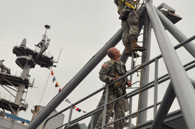 Specialist Charles Manuel, (upper right) and Spc. Courtney Hull, watercraft operators assigned to U.S. Army Logistic Support Vessel 1, climb the forward mast May 27 at Intrepid Pier, New York City, to dress the vessel for Fleet Week. The LSV-1 hosted visitor's throughout the Memorial Day weekend. (U.S. Army photo Sgt 1st Class Kelly Jo Bridgwater)