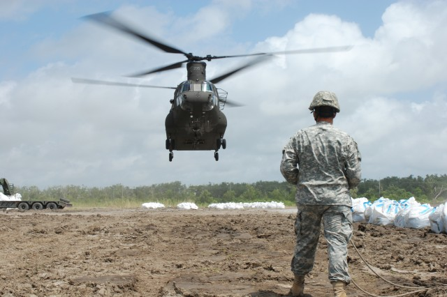 Aviators from the Florida and Mississippi National Guard fly CH-47 Chinook helicopters to assist the Louisiana National Guard's 205th Engineer Battalion with filling breaches in Louisiana's barrier islands with airlifted sandbags, June 5, 2010, near Buras, La.
