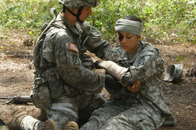 An EFMB candidate administers medical aid to a Soldier on the tactical combat casualty care lane.