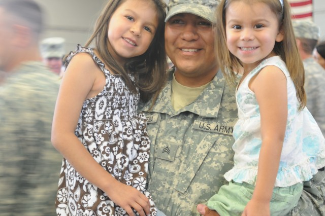 Sgt. Talayumptewa embraces his children for the first time following his 12-month deployment to Kuwait Naval Base, Kuwait. (U.S. Army photo Spc. Krista Howell)