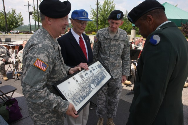 Leaders of the 29th Army Band show Brig. Gen. Frank Batts, right, commander of the 29th Infantry Division, a photo of Virginia Guard's 116th Regimental Band during World War II.  The photo was presented by retired Warrant Officer Ralph E. Shanks, 92, of Martinsville, Va., who commanded the Regimental Band during World War II.