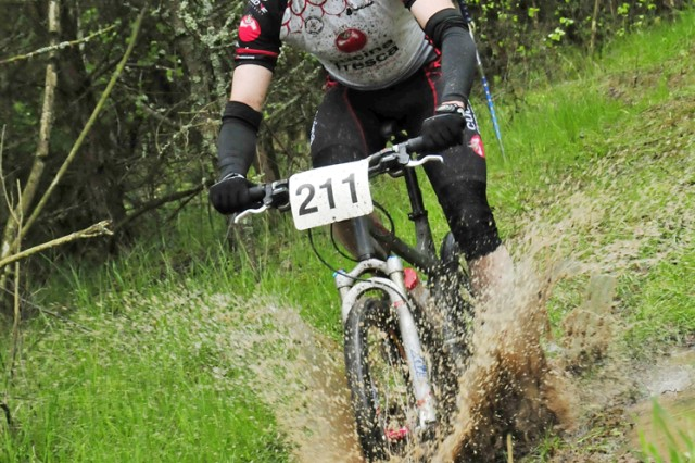 GRAFENWOEHR, Germany - Joe Peterson splashes through a puddle during the 2010 Installation Management Command Mountain Bike Series on May 15.