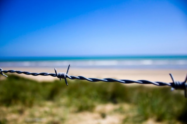 The Norman coast through barbed wire on Omaha Beach, in Normandy, France. Over 90 Army Reserve Soldiers with the U.S. Army Civil Affairs and Psychological Operations Command (Airborne), with units throughout the United States and Puerto Rico, participate in Operation Air Drop Normandy. The operation commemorates the 66th Anniversary of D-day Allied Invasion by visiting key sites, participating in memorial ceremonies and conducting airborne operations on June 5, 2010, on the same drop zones their paratrooper brethren jumped on 66 years ago.
