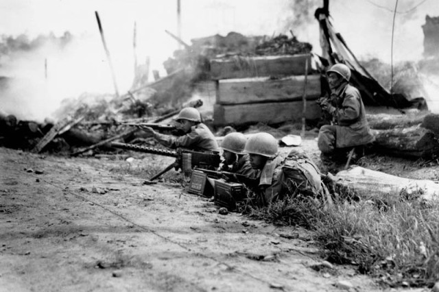 A machine gun crew fires at fleeing Communist-led North Korean targets during heavy street fighting in the captured city of Waegwan. L-r: Pfc. Austin Dela Cruz of Honolulu; Cpl. William Purdy; Pfc. Alexander Domingo of Honolulu; and platoon leader Sgt. Robert I. Muramoto of Honolulu, T.H. 21 September 1950.  Korea. Signal Corps Photo #FEC-50-9336 (Chang)