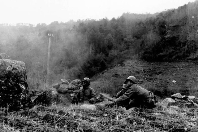 A patrol of Co. C, 65th Infantry Regiment, 3rd Infantry Division, fire light machine guns on Chinese Communist troops located in the hills near Haejung, North Korea. Sfc. Forsyth, who photographed the action, was wounded shortly after recording this picture. 27 November 1950. Korea. Signal Corps Photo #X/FEC-50-22454 (Forsyth)