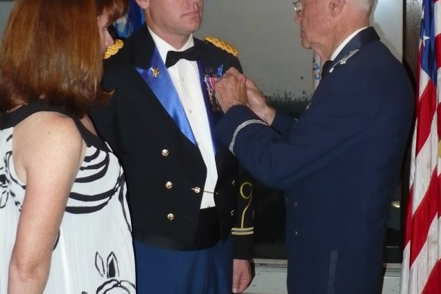 "Chief Warrant Officer 4 Patrick Benson receives the American Legion Valor Award from retired Air Force Col. Norman Schaefer during the 59th annual Valor Award Military Ball on May 16. He received the award in recognition of his ""valiant and heroic actions"" while under attack during combat in Operation Enduring Freedom. With Benson is his wife, Stacey."
