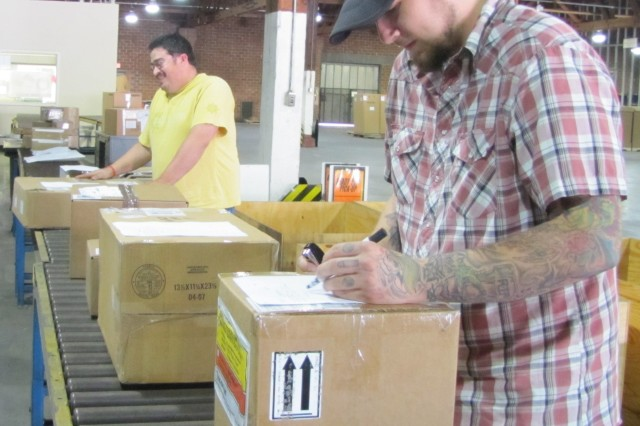 Austin Mason, foreground, and James Griffin doublecheck shipments that will be sent out to Arsenal or Arsenal-related organizations from Central Receiving.