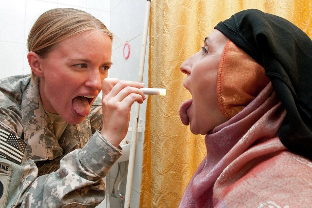 Spc. Aubrey Stoda, a medic with 307th Brigade Support Battalion, 1st Advise and Assist Brigade, 82nd Airborne Division, demonstrates to a patient how to open wide during a one-day, combined U.S.-Iraqi medical clinic June 6 in Kubaysah, Iraq.