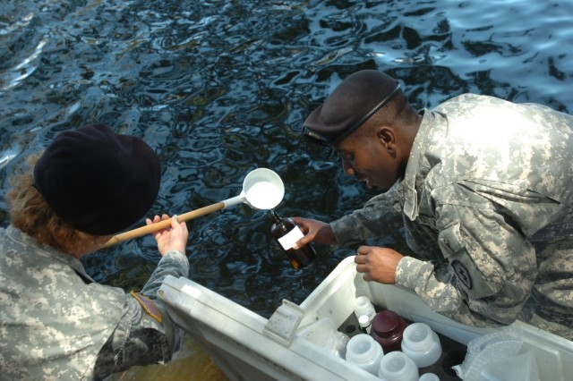 First Lt. Karolyn Braun (left), environmental science officer with 29th Brigade Support Battalion, Hawaii Army National Guard, fills a water sample bottle with Spc. Kellon Belfon, a preventive medicine specialist with 225th Bde. Support Bn., 2nd Bde. Combat Team, 25th Infantry Division, during environmental surveillance training at Lake Wilson, Wahiawa, Hawaii, May 27.