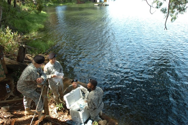 Instructors Capt. Justin Sprague, head of field preventive medicine Public Health Region Pacific, Camp Zama, Japan, and First Lt. Jaree Johnson, chief of medical entomology at the same unit, discuss water sample collection techniques with their students, 1st Lt. Karolyn Braun, environmental science officer with 29th Brigade Support Battalion, Hawaii Army National Guard, and Spc. Kellon Belfon, a preventive medicine specialist with 225th Bde. Support Bn., 2nd Bde. Combat Team, 25th Infantry Division, during environmental surveillance training at Lake Wilson, Wahiawa, Hawaii, May 27.