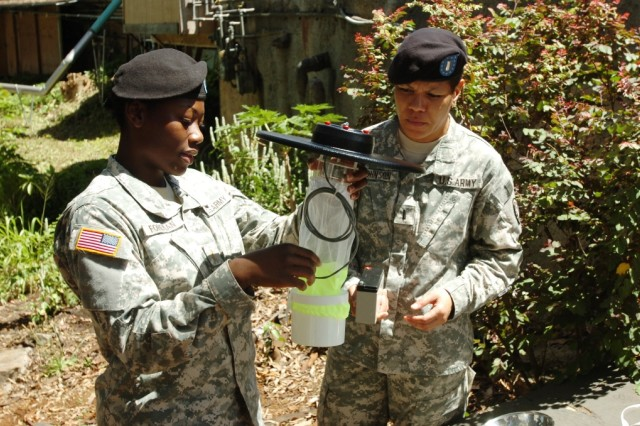 Second Lt. Jennifer Foreman (left), the environmental science officer of 225th Brigade Support Battalion, 2nd Bde. Combat Team, 25th Infantry Division, assembles a 'light trap' to capture mosquitoes for environmental testing, while her instructor, 1st Lt. Jaree Johnson (left), chief of medical entomology, Public Health Region Pacific, Camp Zama, Japan, observes her technique during environmental surveillance training at Lake Wilson, Wahiawa, Hawaii, May 27.