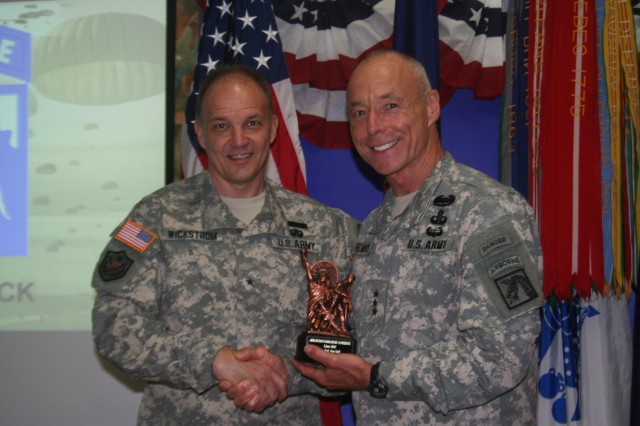 New York Army National Guard Brig. Gen. Steven Wickstrom, commander of the 42nd Infantry Division presents an Empire State Minuteman statue to Lt. Gen. Frank Helmick, commander of the 18th Airborne Corps and Fort Bragg.  Helmick spoke to the Army National Guard's Division Commander's conference in New York City June 4-5 regarding the Army National Guard's future roles in Overseas Contingency Operations.  All eight Army National Guard divisions were represented at the conference.