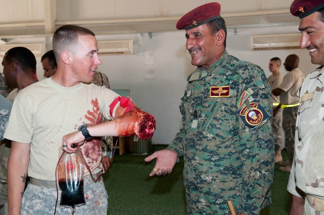 An American paratrooper with 307th Brigade Support Battalion, 1st Advise and Assist Brigade, 82nd Airborne Division, shows a simulated amputation to Sgt. Maj. Faisel of 7th Iraqi Army Division, prior to a mass-casualty training exercise June 3 at Camp Mejid. A bag of fake blood and a pumping mechanism simulate massive bleeding.