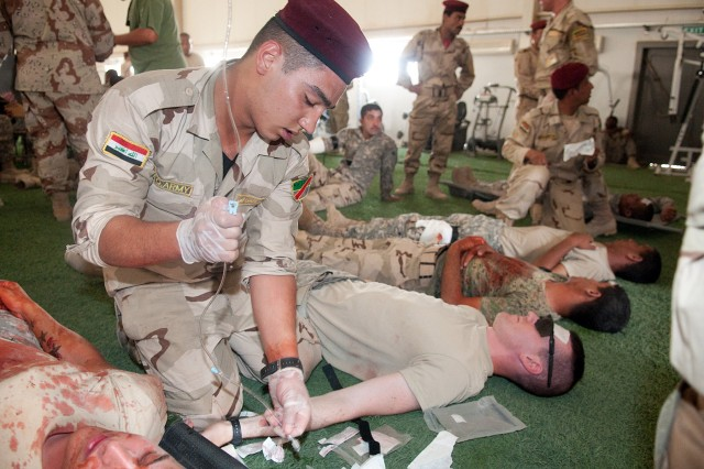An Iraqi medic with 7th Iraqi Army Division, prepares a saline block for a simulated wounded Soldier at a casualty collection point during a mass-casualty training exercise June 3 at Camp Mejid. American mentors called the exercise an outstanding success.