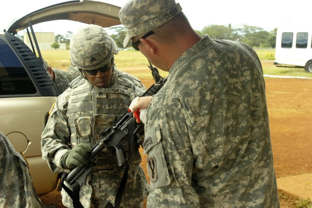 FORT SHAFTER, Hawaii - Sergeant Joseph Smith, 505th Quartermaster Battalion, Okinawa, slides the ejection port of his M4 Carbine Assault Rifle open for Master Sgt. Jerry Queen, ammo point Noncommissioned Officer, 1st Battalion, 196th Infantry Brigade, to lubricate the weapon prior to participating in the weapons qualification event of the U.S. Army Pacific 2010 Warrior Challenge weapon qualification event at Schofield Barracks, Hawaii, June 8. Eleven Soldiers and NCOs each earned the right to compete in the event, testing their physical and mental limits during the five-day competition. Winners will be announced at the Army Commemoration Celebration at the Hilton Hawaiian Village in Honolulu on June 12.