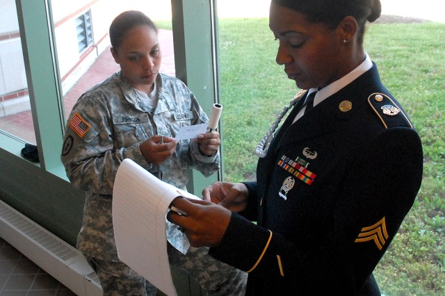 Sgt. Latrisha Howard-Robinson, of Fort Sill, Okla., and her lint-roller wielding sponsor, Sgt. 1st Class Jessenia Johnson, review before her Combined Arms Center Noncommissioned Officer of the Year knowledge assessment board June 3 at Eisenhower Hall, Fort Leavenworth, Kan.