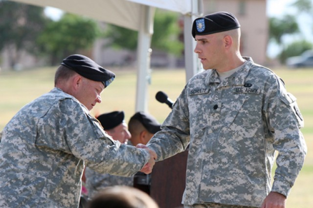Reviewing Officer, Lt. Col. Thomas Miller, left, shakes hands with Lt. Col. Robert Schulte, incoming commander of the 309th Military Intelligence Battalion, after making a brief statement to his new unit during the June 3 change of command ceremony on Brown Parade Field.