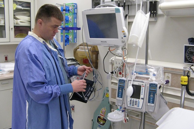 FORT CARSON, Colo.---Spc. Keith A. McCullough, Army medic, prepares equipment in the new trauma room at Evans Army Community Hospital's Emergency Department. The room can accommodate two patients and is bright and spacious.
