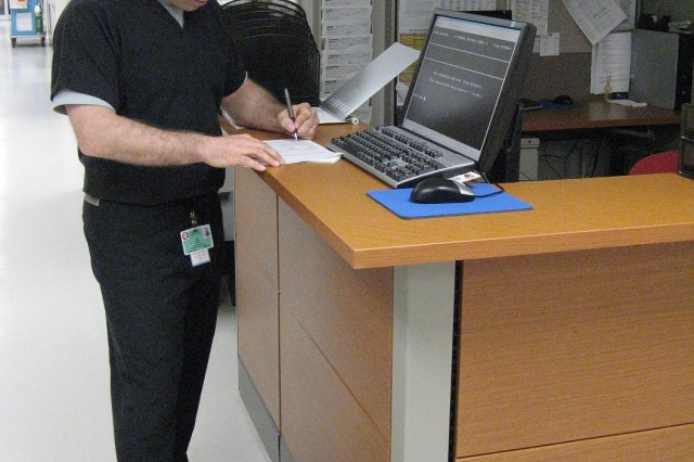FORT CARSON, Colo.---Physicians Assistant Jason D. Barber reviews a patient's records at one of the new administrative stations at Evans Army Community Hospital's Emergency Department.