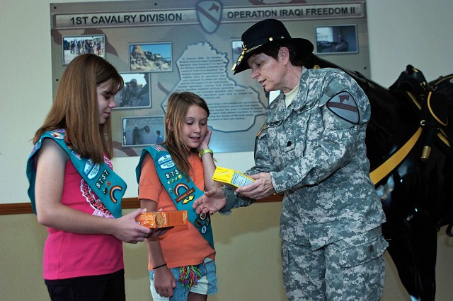 FORT HOOD, Texas - Gillian Herman (left) and Madison Gray, Girl Scouts with Girl Scout Troop 8737, from Frisco, Texas, hand over two of the 116 donated boxes of Girl Scout cookies to Chaplain (Lt. Col.) Barbara Sherer, 1st Cav. Div. chaplain.
